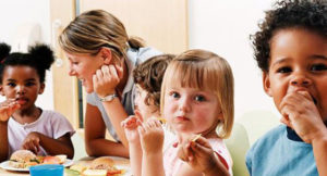 Toddlers eating sandwiches